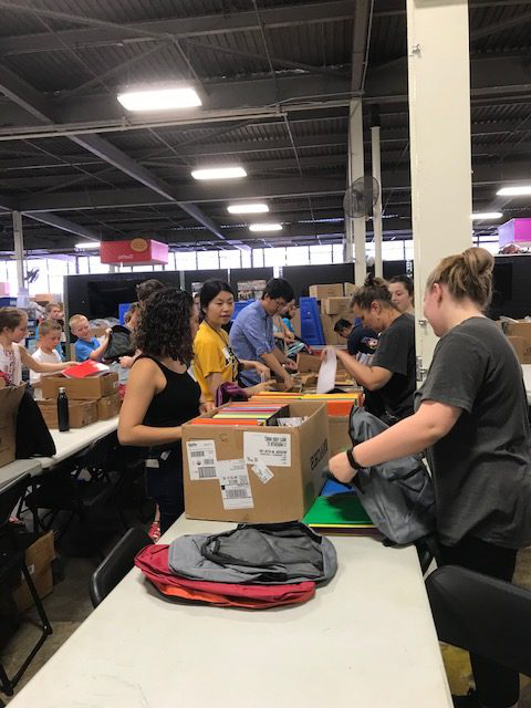 会员 from the Department of Chemistry help assemble backpacks for 摇篮到蜡笔 recipients.