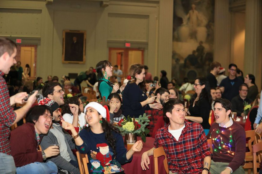Members of the department of chemistry enjoy karaoke in a large ballroom while wearing festive holiday sweaters