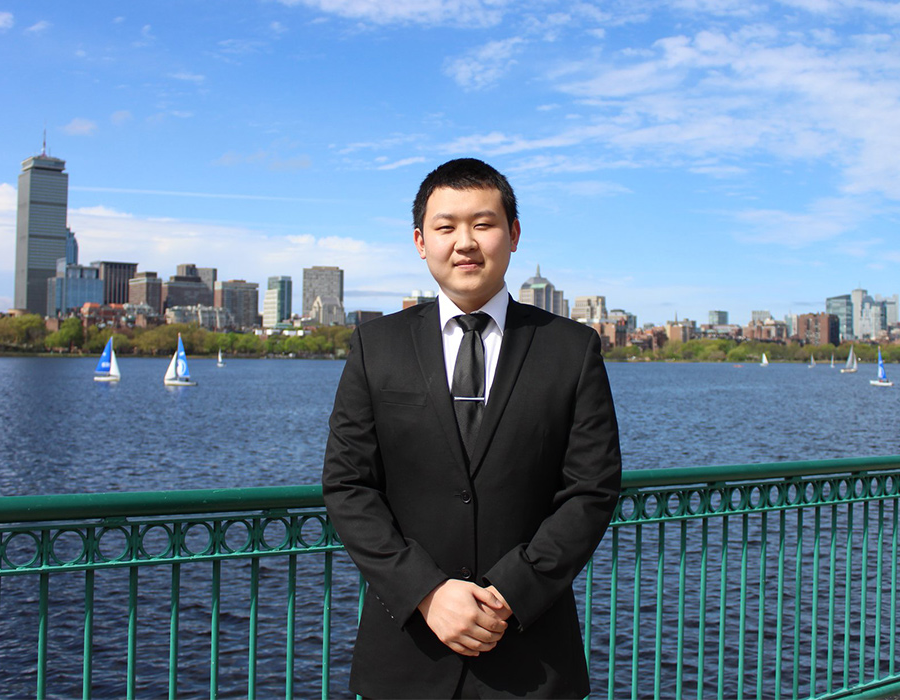 Undergraduate Chemistry Major Miller Tan poses in front of the Boston skyline