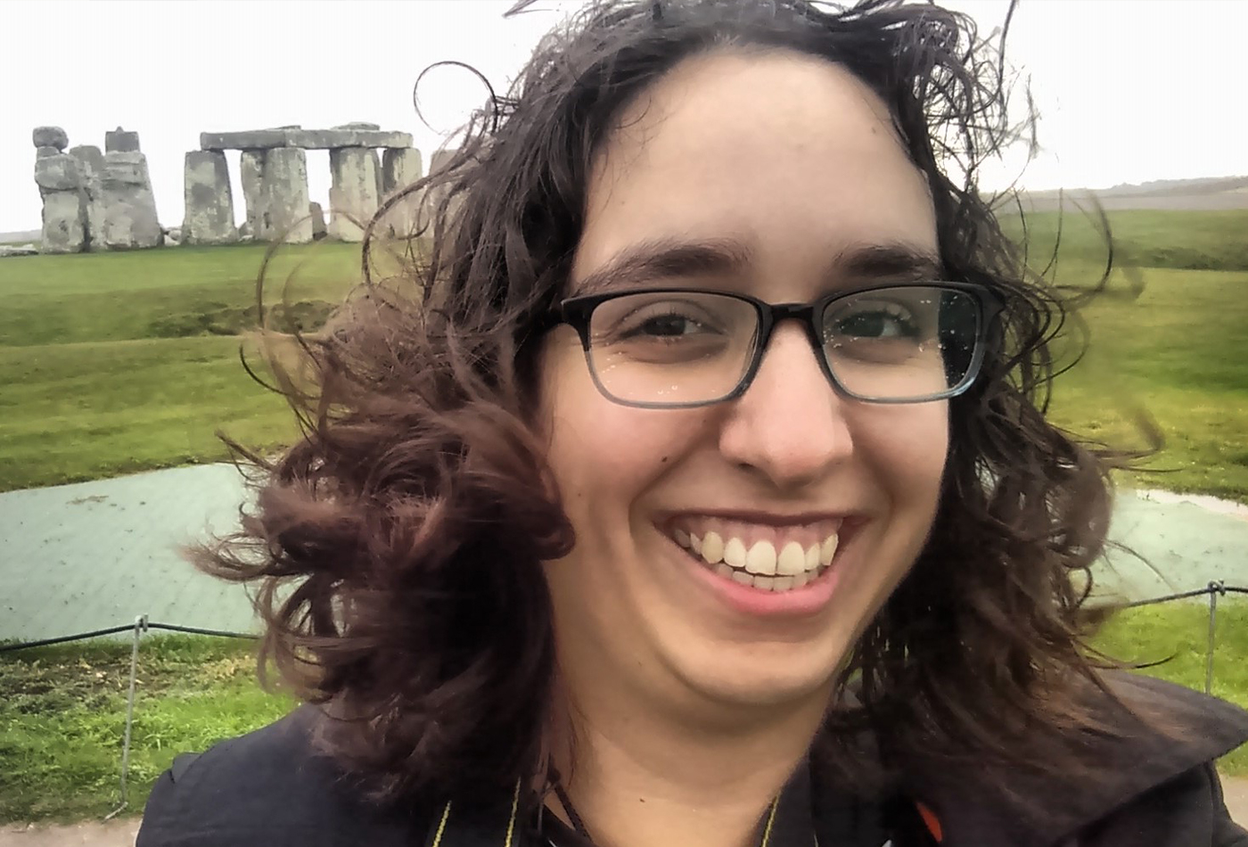 A female graduate student takes a self portrait in front of Stonehenge.