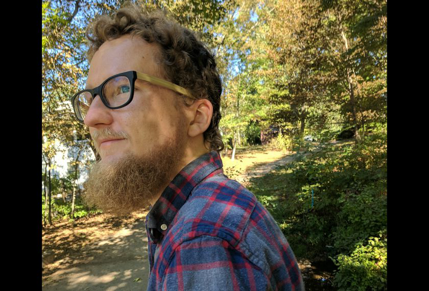 Male graduate student with glasses and a beard gazes into the distance with an autumnal background.